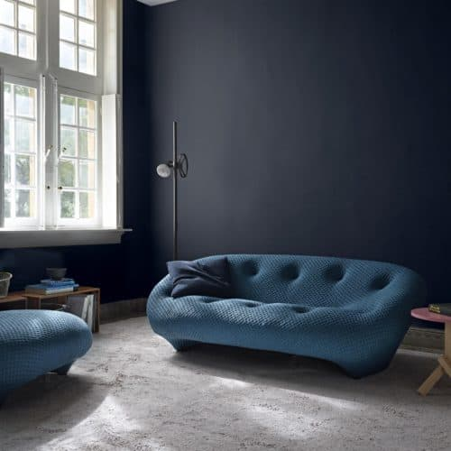 Curved tufted sofa, deep blue walls, Ligne Roset.