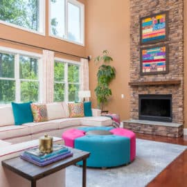 interior design living room tall ceilings colorful art custom draperies curtains white sectional sofa couch blue magenta ottoman