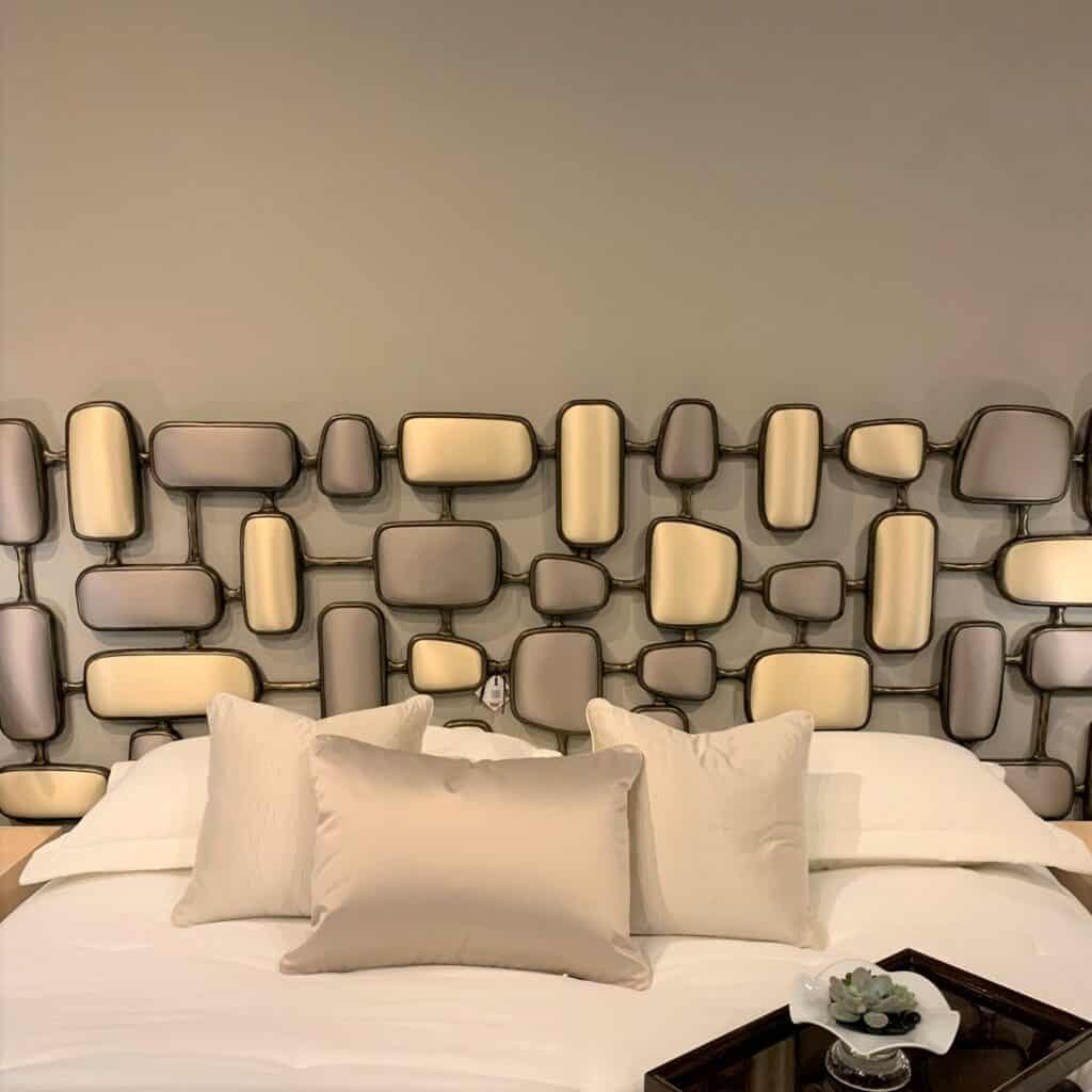 Metal shapes upholstered in solid fabric, two tone. Almost an artwork piece for a headboard.