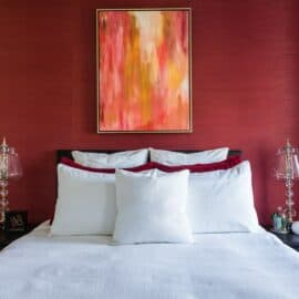 interior design bedroom red wallpaper accent wall yellow gold pink abstract art white bedspread LK Design