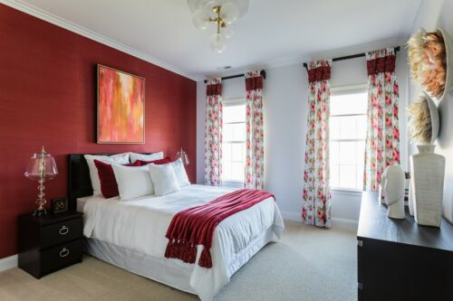 Colorful guest bedroom in red grasscloth wallpaper and white wall. Floral draperies. White bedding.