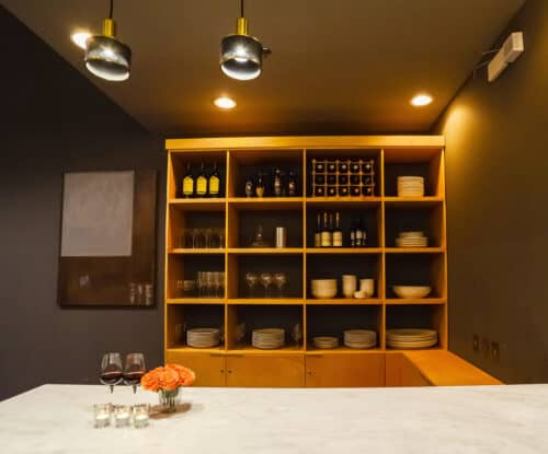 Modern bar with custom designed shelving unit. Marble countertop.