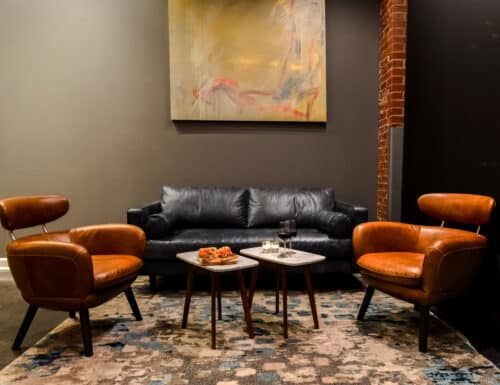Sitting area with leather sofa and chair, marble top tables. Abstract art work in warm tones.