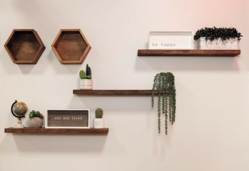 Floating shelves decorated with greenery and word art.