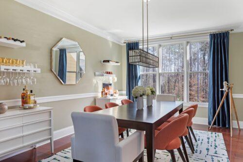 interior designer modern dining room black table orange chairs octagon mirror statement chandelier floral arrangement
