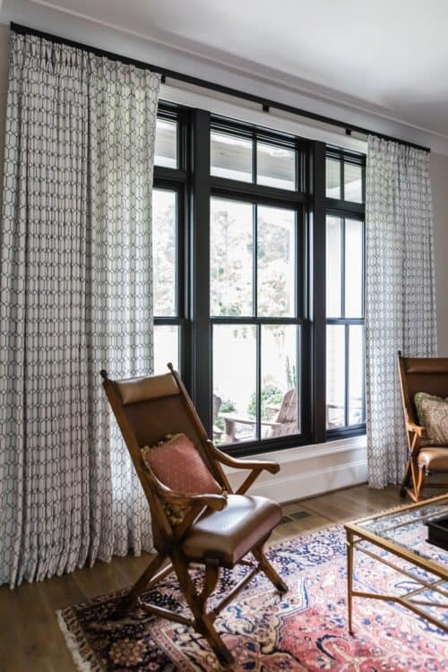 window treatments brown leather chair black window frames curtains Persian rug glass coffee table LK interior Design