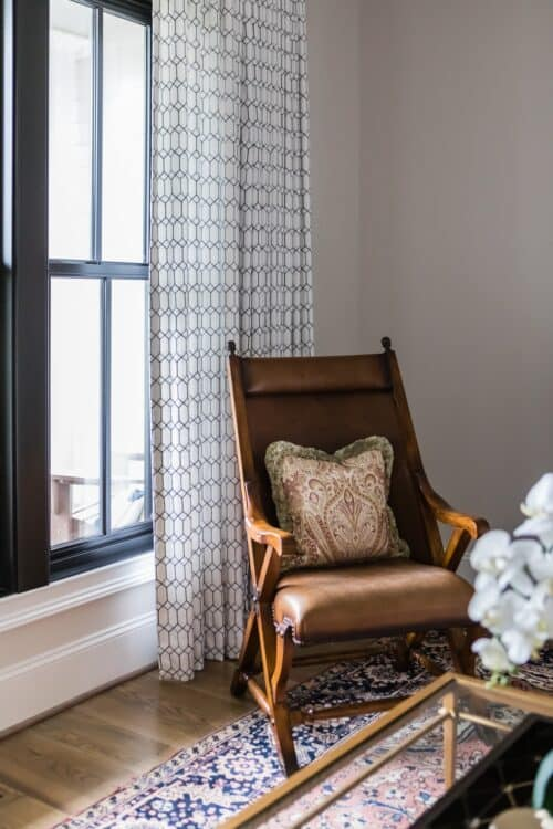 custom window treatments brown leather chair pillow black window frames white curtains Persian rug glass coffee table LK interior Design