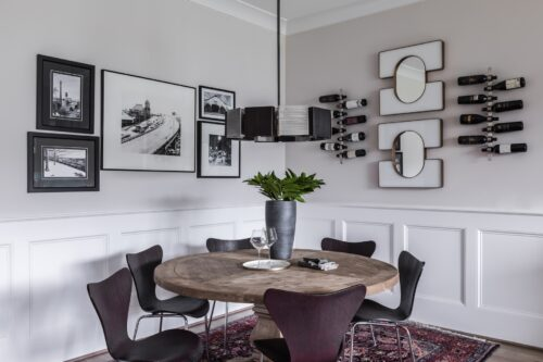 breakfast nook black and white photographs distressed wood table vase cut stems wine rack