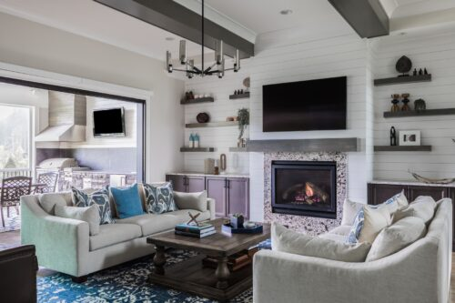 family room floating shelves sofa pillows fireplace built-ins blue patterned rug