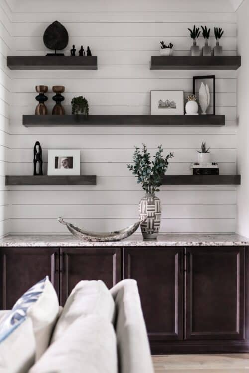 interior design white wall floating shelves figurines collections built-ins art objects photo frames eucalyptus branches LK Design