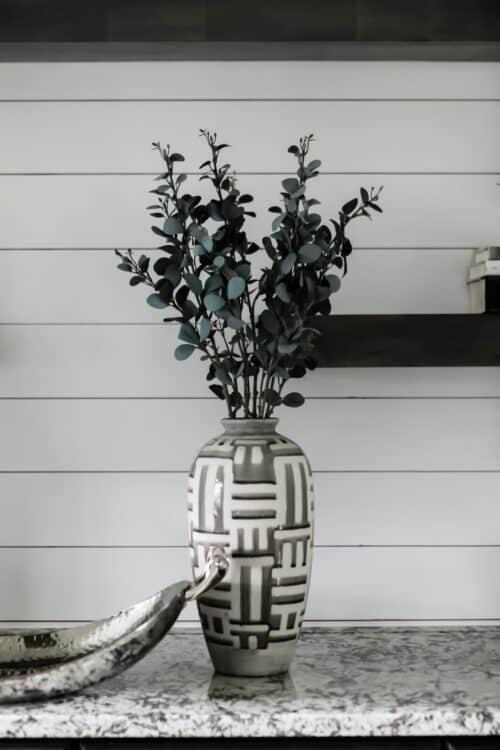 interior design white wall floating shelves patterned vase eucalyptus branches fruit bowl LK Design