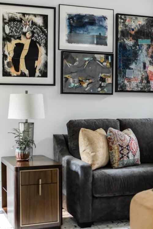 interior design family room gray sofa throw pillows art collection abstract table lamp
