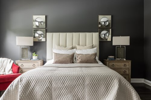 interior design master bedroom gray wall paint beige headboard quilted bedspread red armchair unique lamps