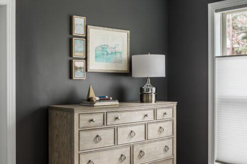 interior design master bedroom light brown wood dresser stack of books framed art collection dark gray walls lamp