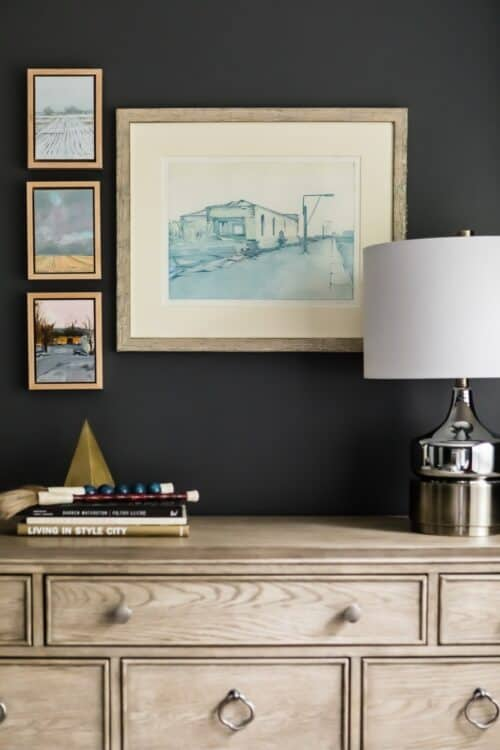 interior design master bedroom light brown wood dresser stack of books framed art collection dark gray walls silver lamp