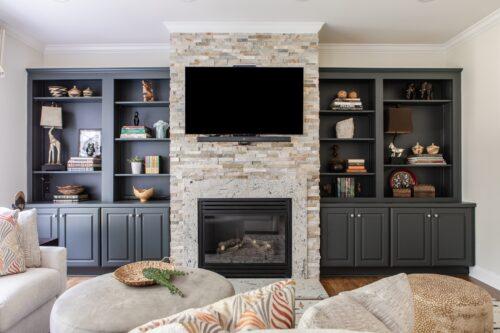 interior design living room cream stone fireplace navy painted shelves