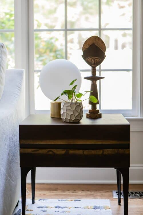 brown wood end table by the window potted plant globe lamp tribal figurine by LK interior design