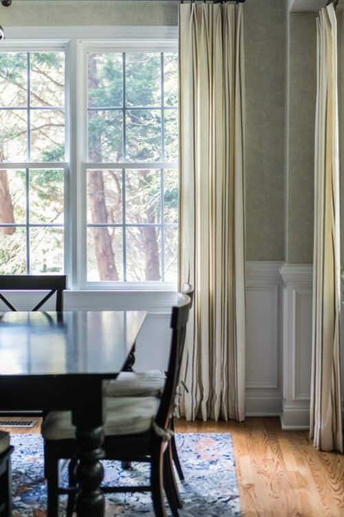 interior design dining room round cream and gold curtains brown wood table and chairs LK Design