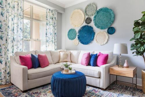 family room white sectional sofa with colorful pillows blue ottoman colorful rug draperies curtains seagrass art