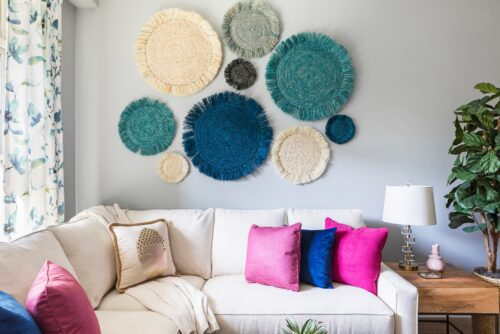 family room white sectional sofa with colorful blue magenta pillows custom draperies curtains seagrass art potted plant
