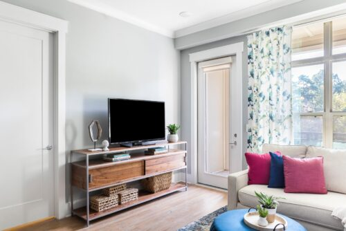 family room white sectional sofa with colorful pillows blue ottoman colorful rug draperies curtains TV stand