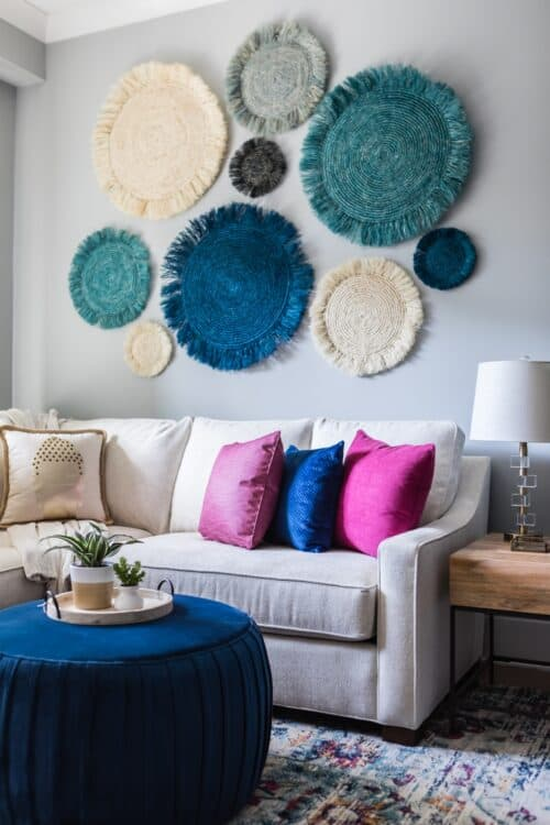 family room white sectional sofa blue magenta pillows colorful rug blue ottoman custom draperies curtains seagrass art potted plants