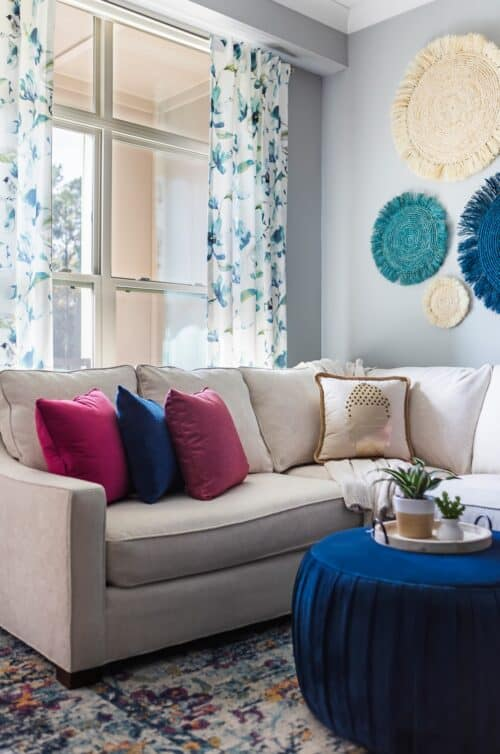 family room white sectional sofa with colorful blue magenta pillows blue ottoman custom draperies curtains seagrass art potted plants