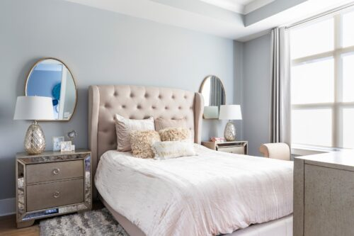 interior design master bedroom gray wall light pink headboard throw pillows gold champagne accents custom window treatments