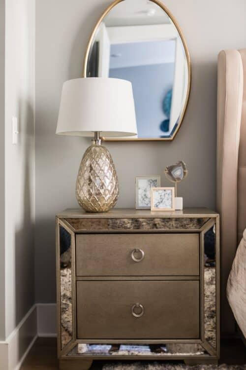 interior design champagne gold lamp night stand dresser oval mirror framed art LK Design