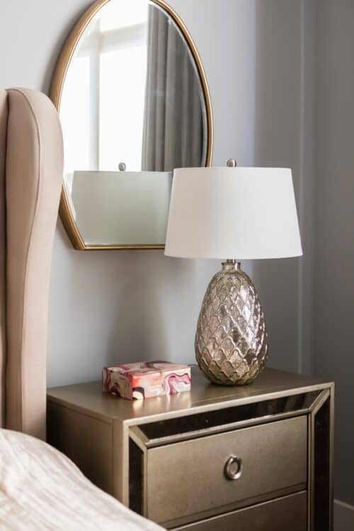 bedroom night stand gold champagne accents lamp oval mirror gray walls light pink accents